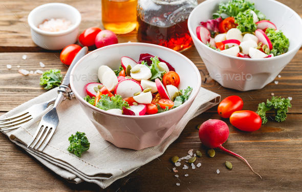 Salad with cherry tomatoes, radsh and mozzarella, lettuce mix - Stock Photo - Images