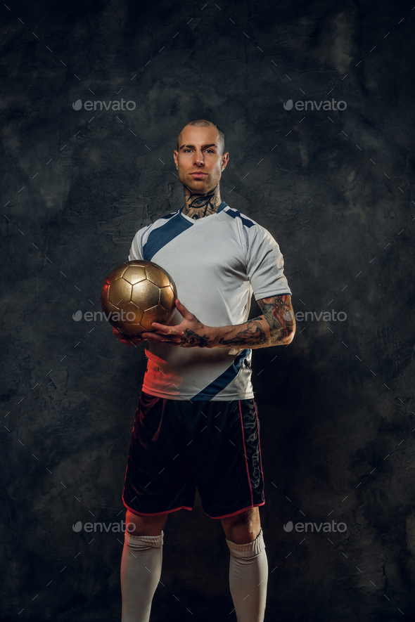 Bold and handsome soccer player holding a golden soccer ball - Stock Photo - Images