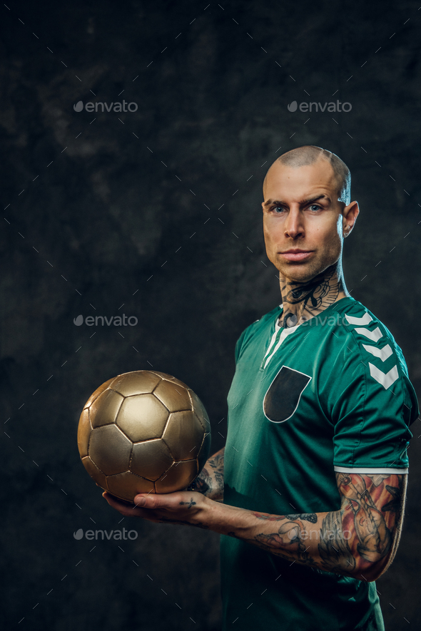 Handsome soccer player holding a golden soccer ball - Stock Photo - Images