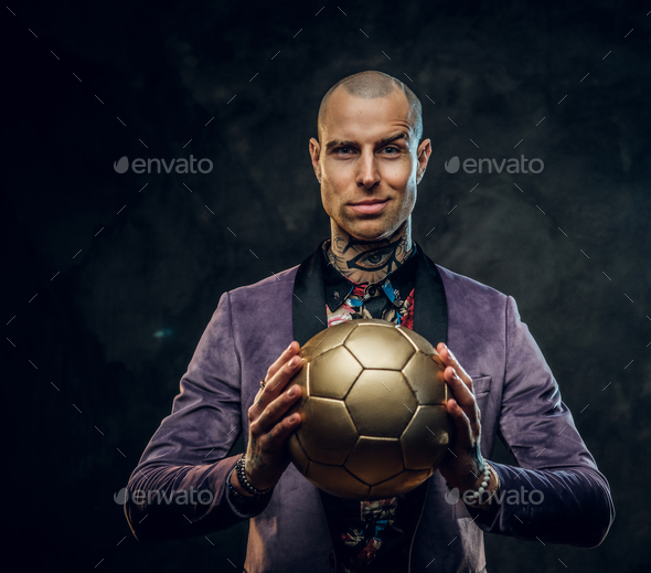 Elegant tattooed male model posing with a golden soccer ball in a studio - Stock Photo - Images