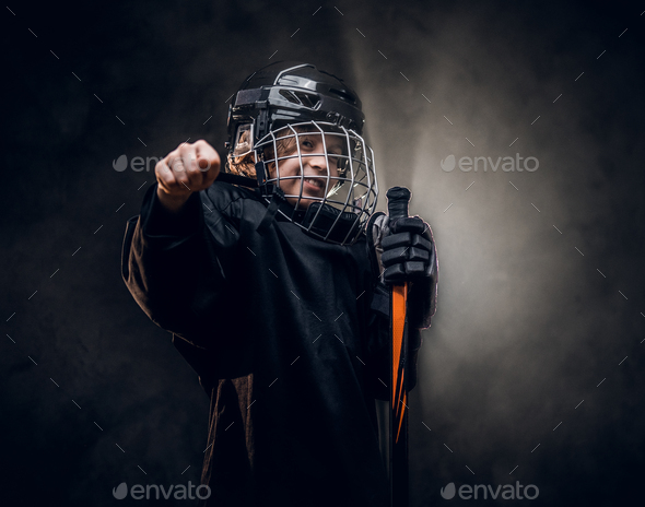 Young hockey player posing in uniform for a photoshoot in a studio - Stock Photo - Images