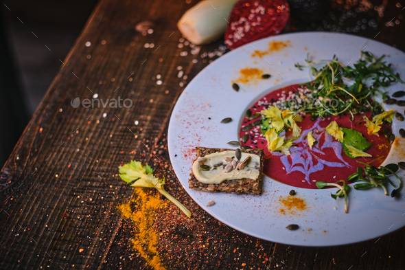 Healthy vegetarian beetroot sauce which includes green sprouts and herbs served on a porcelain dish - Stock Photo - Images