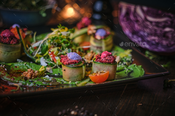 Haute cuisine vegetarian plate of appetizer rolls and a bowl of herbs served on a wooden table - Stock Photo - Images