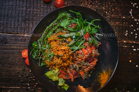 Cooked vegetarian bowl of plov on a wooden table - Stock Photo - Images