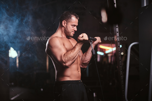 Fit sportsman in a dark gym surrounded by smoke - Stock Photo - Images