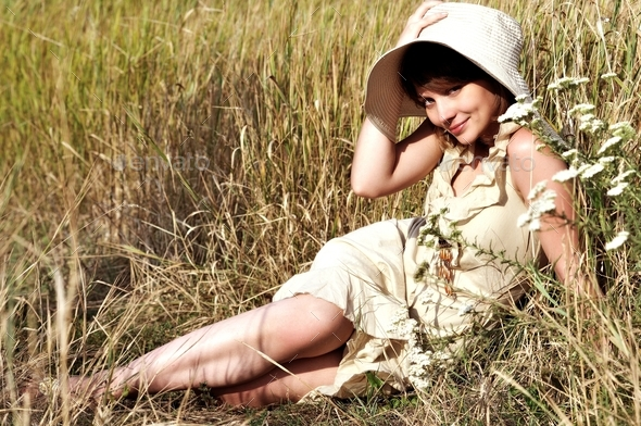 Woman lying on summer field among flowers - Stock Photo - Images