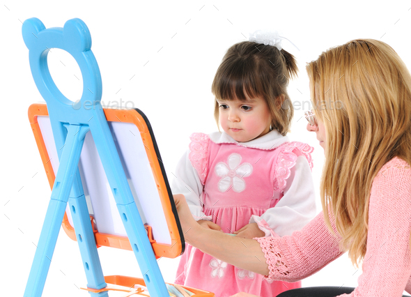 Girl with mom draw on blackboard together - Stock Photo - Images