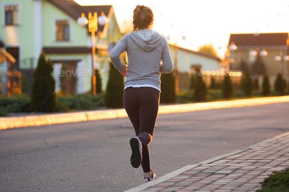 Young female runner, athlete is jogging in the city street in sunshine. Beautiful caucasian woman - Stock Photo - Images