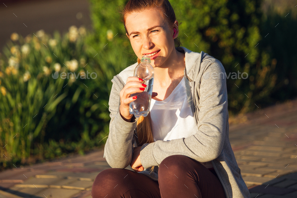 Young female runner, athlete resting after jogging in the city street in sunshine. Beautiful - Stock Photo - Images