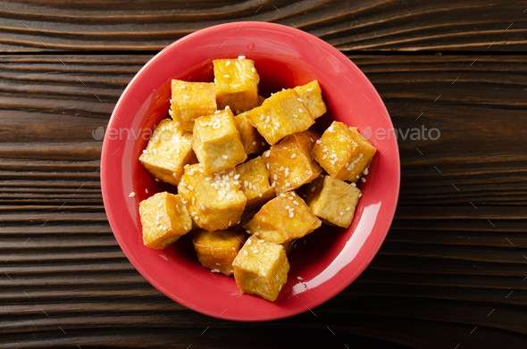 Flat lay closeup view at crispy deep stir fried tofu cubes with chives in clay dish - Stock Photo - Images