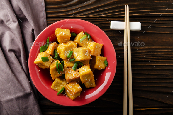 Flat lay view at crispy deep stir fried tofu cubes with chives in clay dish - Stock Photo - Images