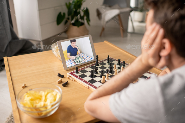 Deciding about chess move while playing with friend via video chat - Stock Photo - Images