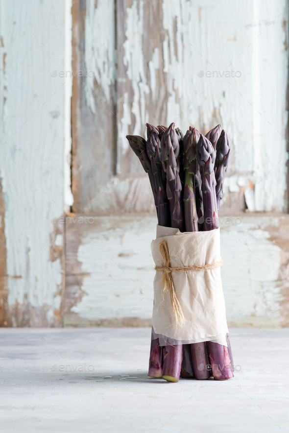 Raw organic purple asparagus spears ready for cooking healthy diet food on a light stone background - Stock Photo - Images