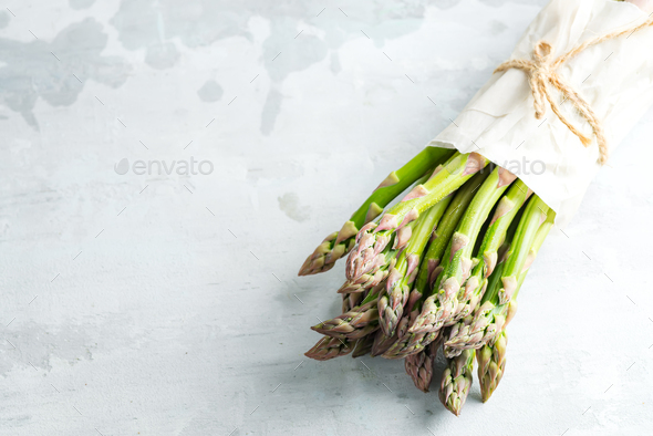 Vertical standing home grown fresh natural organic green asparagus bunch against stone background - Stock Photo - Images