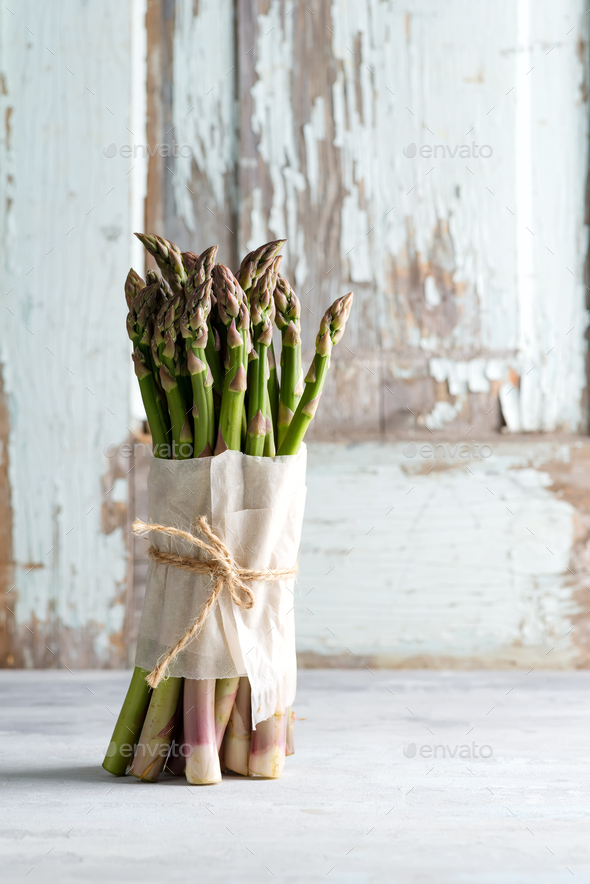 Freshly picked natural organic green asparagus bunch on light stone background - Stock Photo - Images