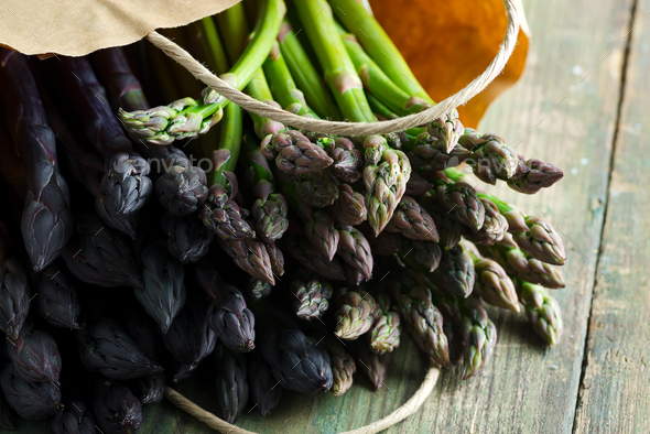 Paper bag with freshly picked raw organic natural purple asparagus spears on a wooden background - Stock Photo - Images