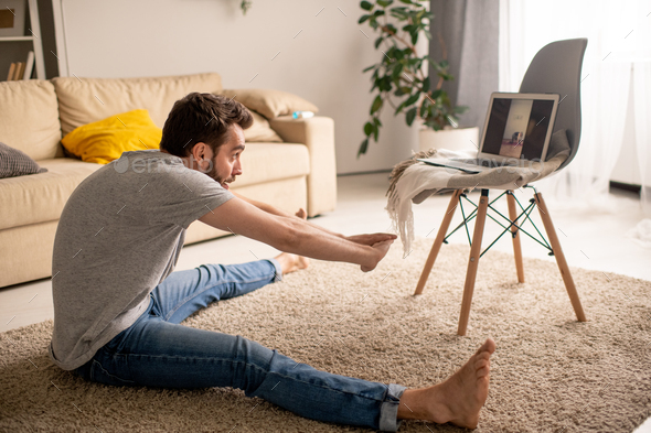 Practicing wide angle seated forward bend at online class - Stock Photo - Images