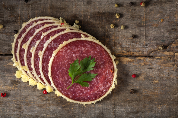 Slices of salami surrounded by parmesan cheese - Stock Photo - Images