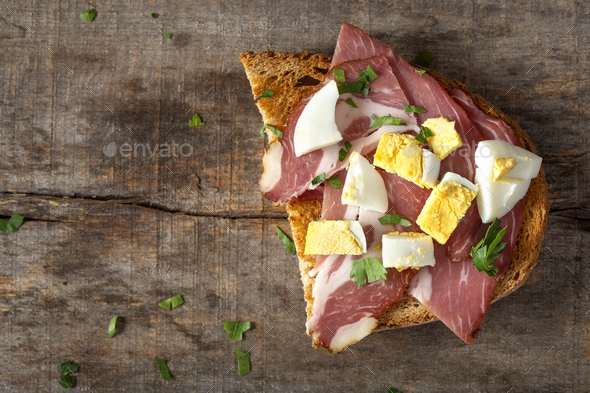 Open sandwich with pork meat, pieces of boiled eggs and chopped parsley - Stock Photo - Images