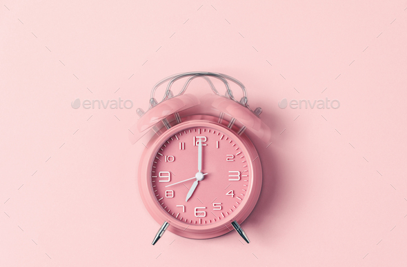 Classic pink alarm clock ringing at seven o'clock against pastel pink background - Stock Photo - Images