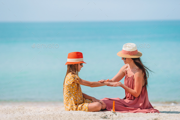 Young mother applying sun cream to daughter nose on the beach. Sun protection - Stock Photo - Images