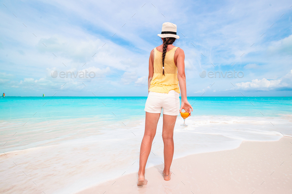 Young beautiful woman having fun on tropical seashore. Happy girl background the blue sky and - Stock Photo - Images