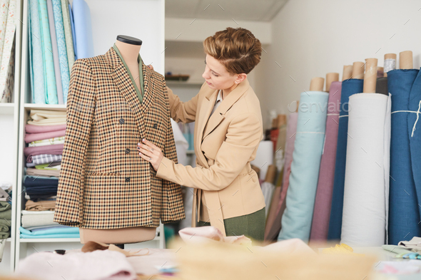 Tailor working with jacket in workshop - Stock Photo - Images