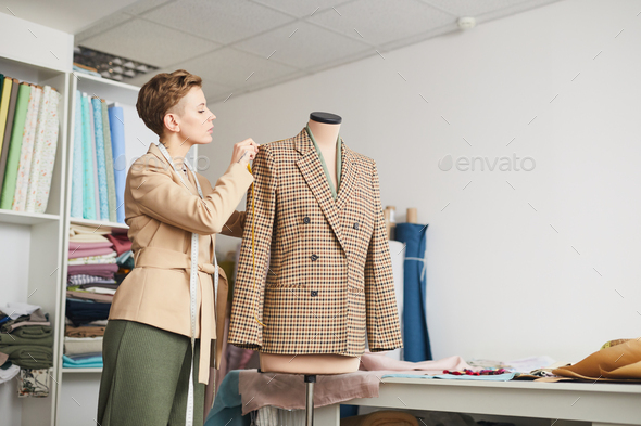Tailor taking measurements from the jacket - Stock Photo - Images