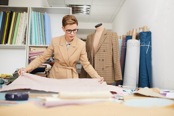 Tailor working with fabric in workshop - Stock Photo - Images