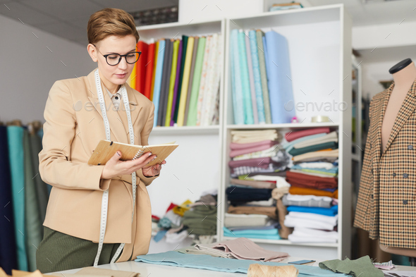 Tailor reading her notebook - Stock Photo - Images