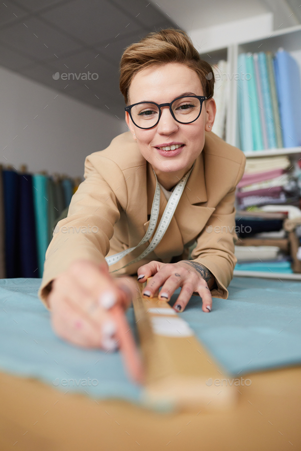 Tailor measuring the fabric - Stock Photo - Images