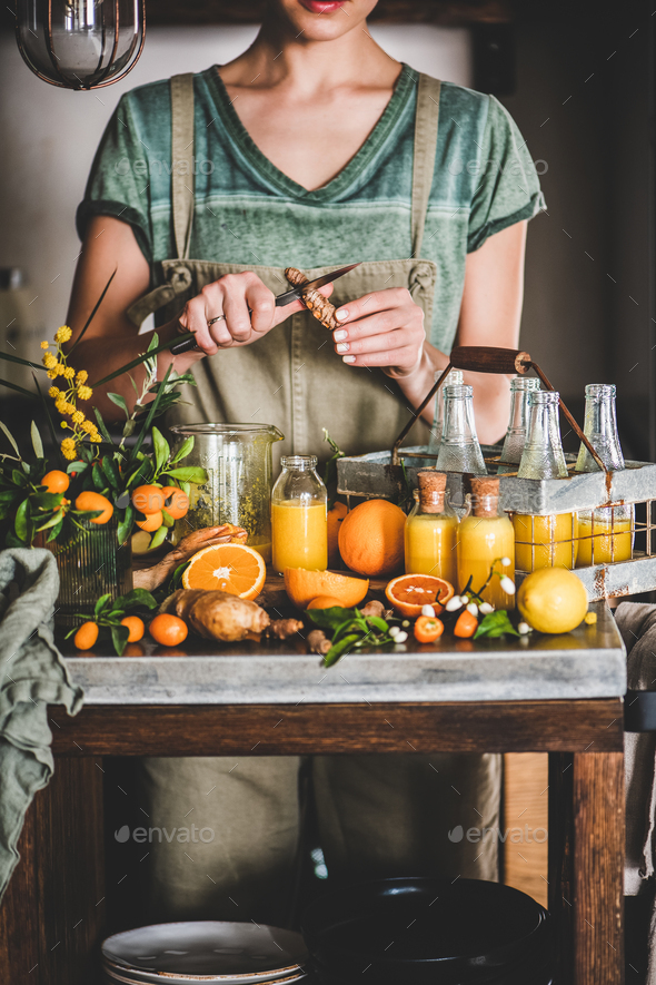 Young woman making fruit immune boosting drink to resist virus - Stock Photo - Images