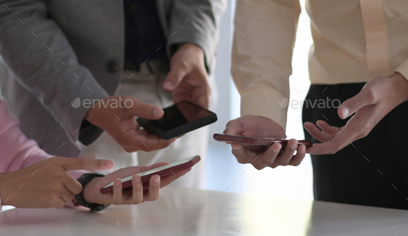 Many employees hold their smartphones near each other to exchange wireless data. - Stock Photo - Images