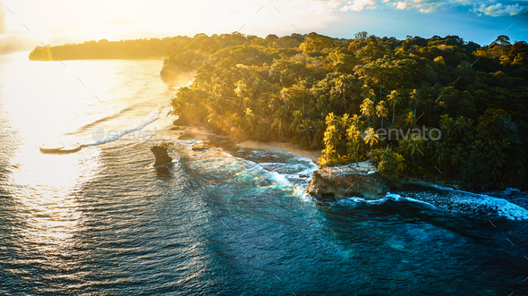 Scenic aerial shot of a tiny rock island surrounded by waves of the crystal clear ocean - Stock Photo - Images