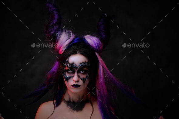 Young woman wearing fantasy dark make-up and violet horns posing in a studio - Stock Photo - Images