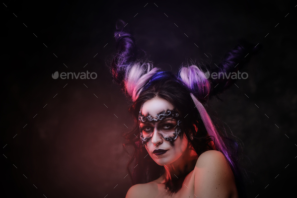 Cosplayer girl wearing dark demonic make up and horns posing in a studio on a dark background - Stock Photo - Images