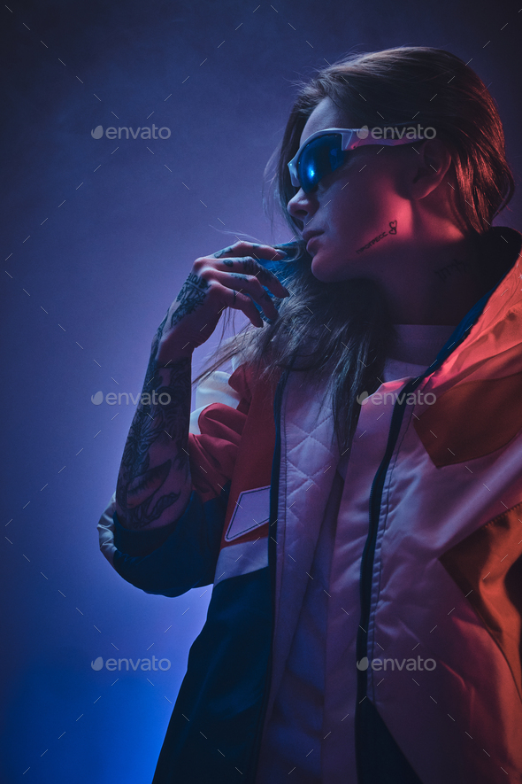 Inked attractive female posing in a neon vivid lights of a studio surrounded by smoke - Stock Photo - Images