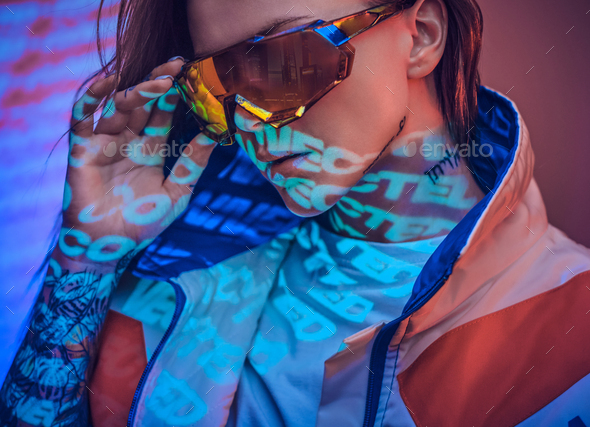 Close up portrait of a young tattooed racer woman posing in a vivid neon studio over text projection - Stock Photo - Images