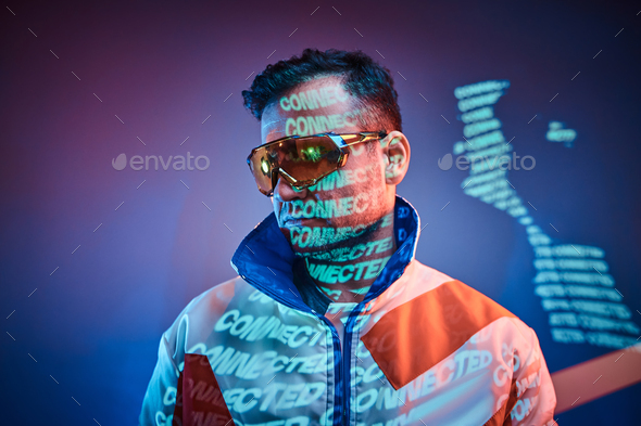 Inked attractive male posing in a neon vivid lights of a studio with text, looking cool - Stock Photo - Images