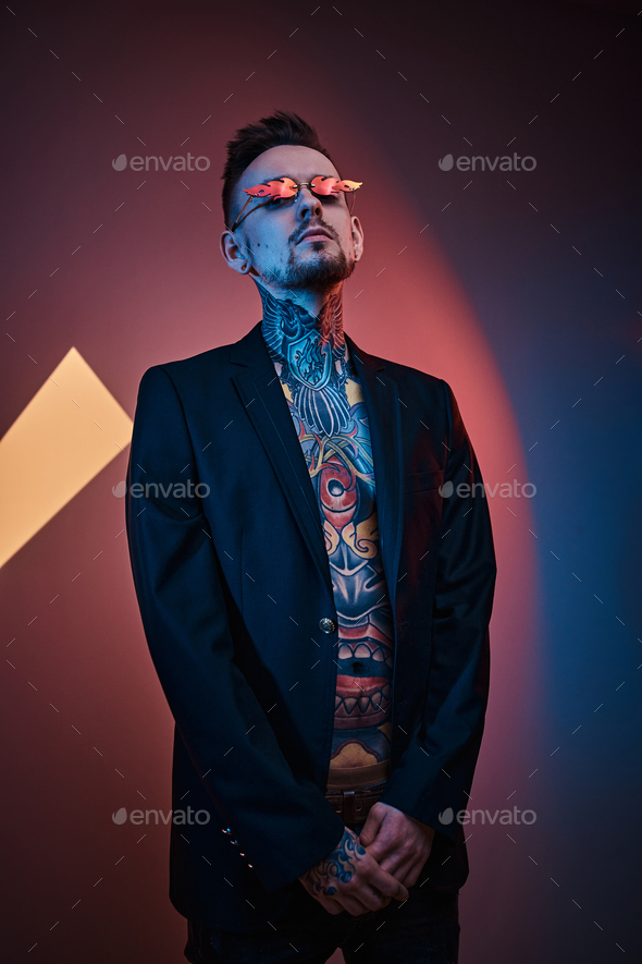 Tattoo artist male model posing in a neon studio with half-naked body, tuxedo and sunglasses. - Stock Photo - Images