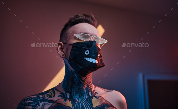 Inked male model posing in a neon studio with half-naked body, sunglasses and medical mask - Stock Photo - Images