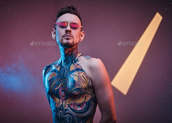 Inked male model posing in a neon studio with half-naked tattooed body and sunglasses. - Stock Photo - Images