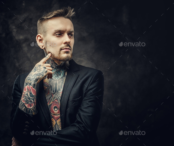 Confident and inked tattoo artist male model posing in a dark studio - Stock Photo - Images