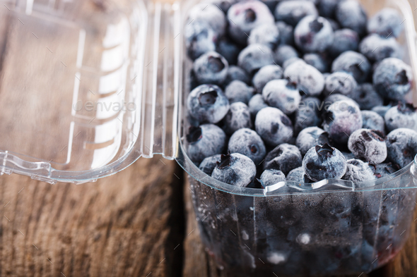 Blueberries frozen in a plastic container. - Stock Photo - Images