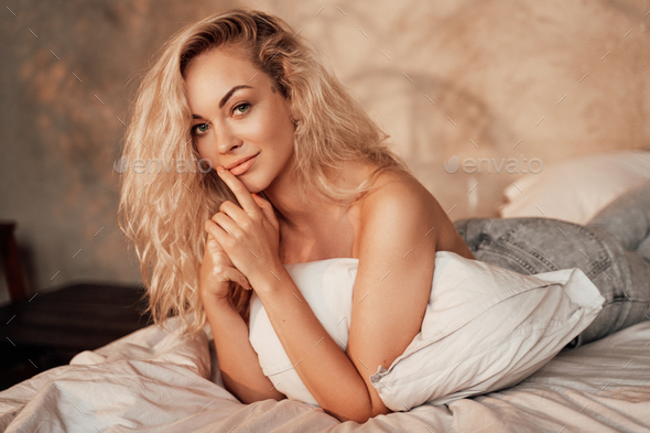 Portrait of attractive and hot woman with fit body wearing only jeans posing while laying in bed - Stock Photo - Images