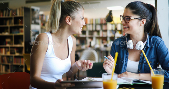 Positive young students girls studying together, preparing for exam - Stock Photo - Images
