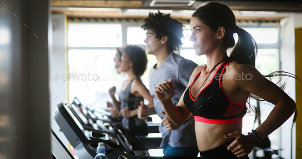 Group of young people exercising on a treadmill at gym - Stock Photo - Images