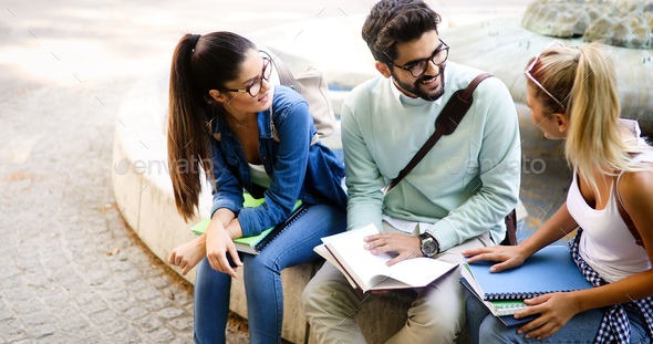 Group of happy students studying, preparing together for exam ourdoor - Stock Photo - Images