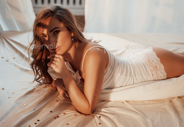 Portrait of a young and beautiful woman in white lace lingerie laying in a cozy bed - Stock Photo - Images