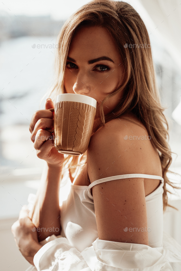 Graceful young woman in lingerie posing with a cup of coffee over the white background - Stock Photo - Images